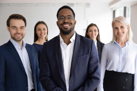 Diverse professionals bank employees company staff members in formal wear, 5 businesspeople lead by African ethnicity leader posing standing together in office. Young aged specialists portrait concept Stock Photo