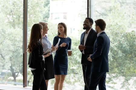 Five successful different age and ethnicity office employees chatting standing in office hall against panoramic window take break resting after seminar, wait negotiations start, feels prepared concept