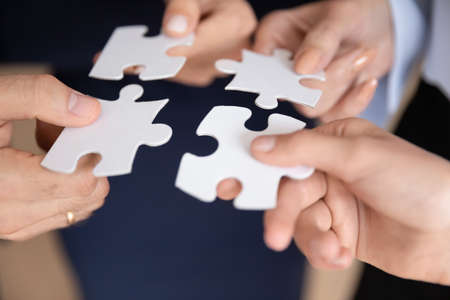 Close up hands of associates four teammates holding white pieces of puzzles, people search and find right solution, best match decision. Team building activity, teamwork, support synergy concept image