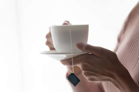 Crop close up of female hands hold white porcelain mug with bag inside, drink hot black green tea at home, woman client enjoy warm brew or beverage in cup, relax rest having break indoors