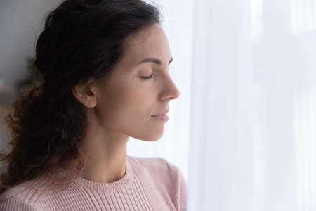 Close up of calm young Caucasian woman stand with eyes closed thinking or pondering, distracted peaceful millennial female lost in thoughts, meditate or relieve negative emotions, breathe fresh air 写真素材