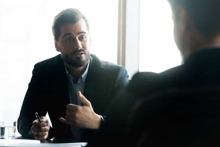 Focus on 30s businessman in formal wear sitting at negotiations table with partner, discussing collaboration details indoors, serious male leader sharing opinion with colleague at briefing meeting.