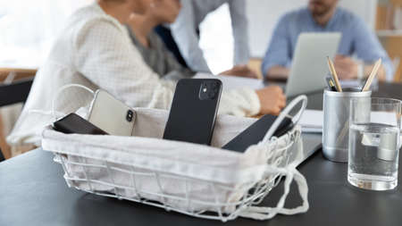 Close up of employee place smartphone gadgets in basket attending no cell office meeting or briefing, workers businesspeople put cellphones in box, brainstorming at conference in boardroom together