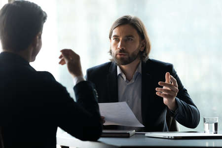 Serious young executive manager with long hairstyle in formal suit discussing business agreement details with focused male partner at negotiation meeting, hr holding job interview with candidate.