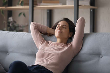 Happy millennial woman sit rest on comfortable couch in living room with eyes closed, take nap sleep or daydream, calm young female relax in sofa at home, breathe fresh air, stress free concept 版權商用圖片
