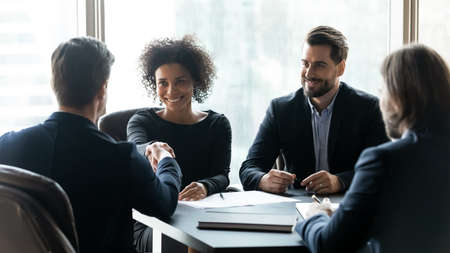 Happy multiracial partners establishing partnership, shaking hands at negotiations meeting. Confident businessman shaking hands with smiling african american female professional, thanking for help.