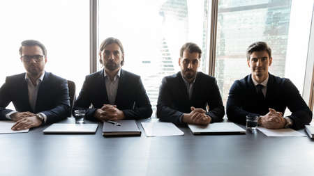 Group of focused male professional headhunters recruiters sitting at table, waiting for job candidate for interview. Serious hr managers teammates in formal wear looking at camera, hiring process. Stock fotó - 151824659
