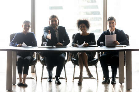 Group of happy young mixed race colleagues hr managers in formal wear sitting together at table, reaching out hand for welcoming promising job candidate at interview meeting in modern office.
