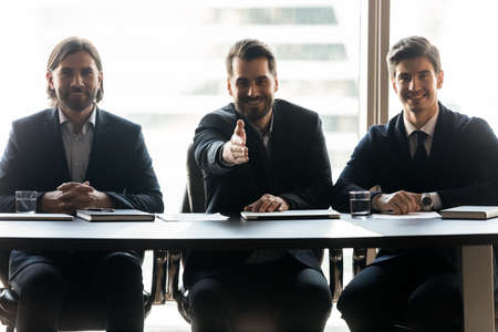 Smiling friendly young male hr managers in suits sitting at table, looking at camera, stretching hand for welcoming promising job seeker, making recruitment offer or greeting newcomer, hiring process.