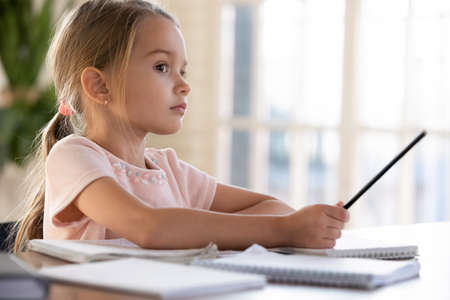 Close up thoughtful little girl sitting at desk, studying at home, pondering school homework, assignments, holding pencil, watching online video course, remote education, homeschooling