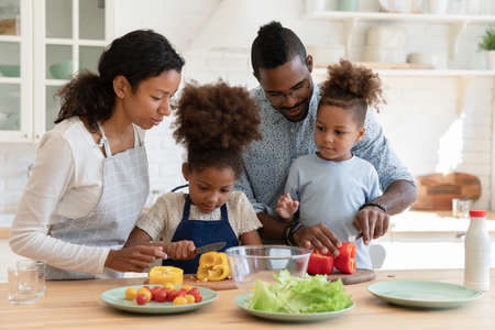 Loving african American mom and dad teach cooking chop vegetables with excited little children in kitchen, happy caring biracial parents prepare food organic salad with small ethnic kids at home