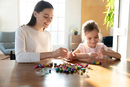 Smiling young mother and adorable little daughter making colorful beads jewelry, sitting at desk at home, happy mum and preschool girl enjoying creative activity, leisure time on weekend
