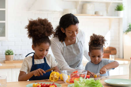 Loving young african American mother or nanny teach little kids prepare healthy food or salad at home kitchen, caring happy biracial mom cooking together with small ethnic children son and daughter