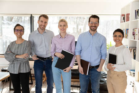 Portrait of smiling multiracial businesspeople posing together in office, show unity and support in work, happy diverse multiethnic employees professional workers look at camera, employment concept