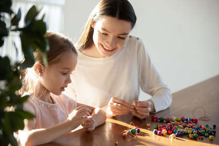 Close up loving mother helping little daughter making colorful wooden beads jewelry, sitting at desk at home, smiling young mum and preschool pretty girl enjoying creative activity, leisure time