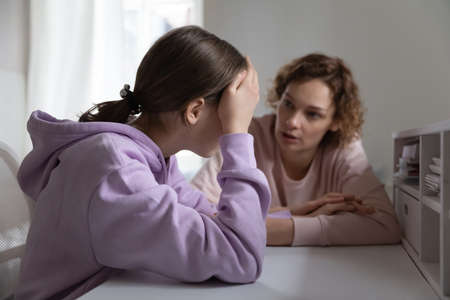 Strict mother scolding upset depressed teenage daughter for bad marks or school exam results, angry mum lecturing lazy unmotivated teen girl, generations, parent and child conflict
