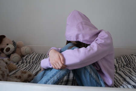 Lonely stressed teenage girl wearing hood sitting on bed alone, crying, thinking about troubles, hiding face, sad upset teenager feeling misunderstood and lonely, child and psychological problem