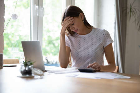 Disappointed young Caucasian woman sit at desk managing household finances or budget frustrated by debt or failure, unhappy distressed female have problems with payment, calculate expenditures Imagens