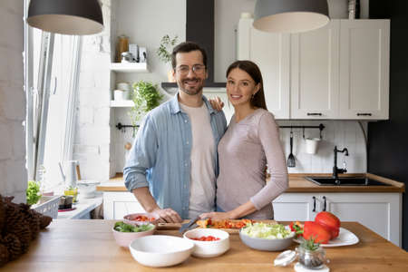 Portrait of happy young Caucasian family stand posing in modern renovated kitchen cooking together, smiling millennial couple renters prepare healthy food at home, moving to new shared apartment