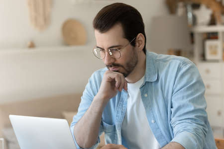 Pensive millennial Caucasian man in spectacles look at laptop screen having problems with slow internet or operation system, thoughtful young male work on computer, think ponder or make decision