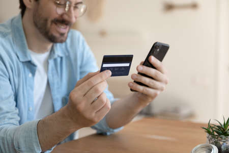 Close up of smiling young Caucasian man hold cellphone make online payment purchase with credit card, happy male shopping online on smartphone, use internet banking service system on gadget