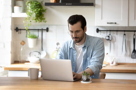 Young Caucasian male in glasses sit in kitchen work freelance on modern laptop at home, focused millennial man look at computer screen, browse surf internet on gadget, technology concept 写真素材