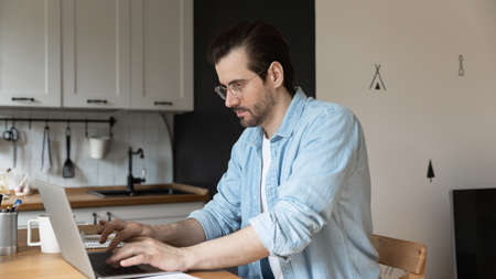 Concentrated young Caucasian man in glasses look at laptop screen browsing surfing web on laptop at home, focused millennial male freelancer work distant online on computer, sitting at kitchen counter