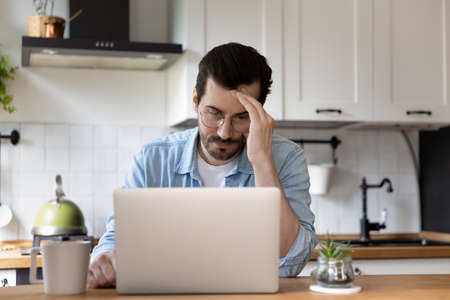 Unhappy Caucasian man in glasses look at laptop screen distressed with bad email message on laptop, stressed young male frustrated by eviction notice or dismissal letter on computer, fail concept