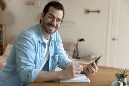 Portrait of smiling millennial Caucasian man in glasses use smartphone make notes in notebook, happy young male study online watch webinar on cellphone handwrite summarize, distant education concept