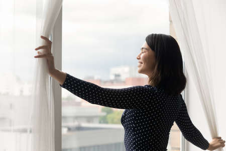 Overjoyed millennial Asian girl open curtains at home meet welcome new sunny early morning in own apartment or home, happy Vietnamese young woman smile for bright future, stress free concept