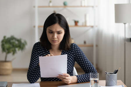 Anxious pensive Asian young woman sit at desk at home reading news notification in post letter correspondence, worried Vietnamese millennial girl consider postal paper document or notice