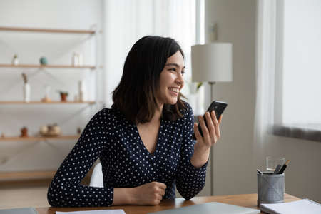Smiling Vietnamese millennial girl sit at desk at home using smartphone look in distance dreaming thinking, happy Asian young woman distracted from cellphone visualize imagine success opportunities