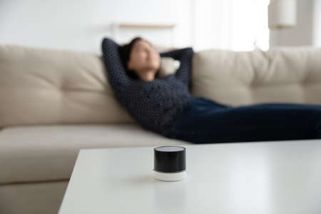 Focus on mini modern smart wireless speaker on table, woman relax rest on sofa in living room at background, female listen to music good quality sound loudspeaker audio device on couch