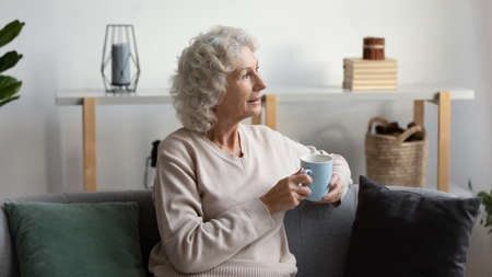 Senior grey haired woman sit on couch in light living room holding mug with beverage start new day enjoy retired tranquil life relaxing looks out the window. Harmony and leisure, weekend at cozy home