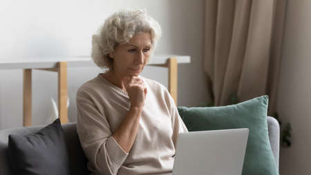 Elderly woman sit on couch at home put portable computer on laps looking at electronic wireless gadget screen feels bewildered, older generation having troubles using modern technology device concept