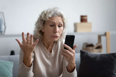 Older generation and modern technology problems of usage, not understand need help concept. Old grey haired woman sit on sofa holds smart phone looks at device screen gesturing feels annoyed and angry Standard-Bild