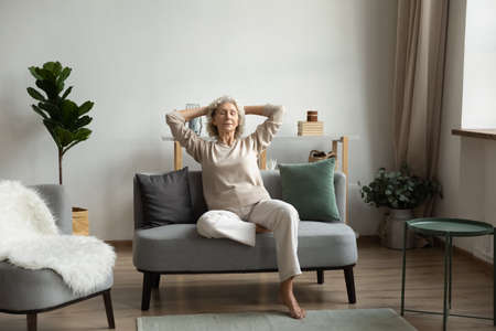 In light living room on modern comfy couch rest aged woman, grandma closed eyes enjoy peace and placidity, put hands behind head breath fresh humidifier air. No stress, carefree retired life concept