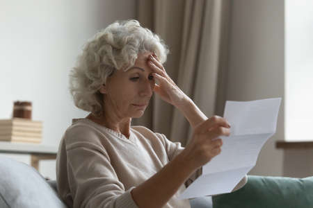 Disappointed elderly woman sitting on couch in living room feels frustrated by bad news, reading paper postal correspondence, bank notice about debt, notification of eviction, negative letter concept