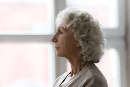 Side profile view face of elderly serious grey haired female standing indoors near window. Age-related natural changes aging process of women, geriatrics branch of medicine, senile diseases concept Standard-Bild