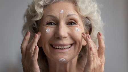 Close up view senior adult woman smile looking at camera applying nutritious or moisturizing facial cream feels happy. Skincare of older generation female, anti wrinkle protective treatment ad concept