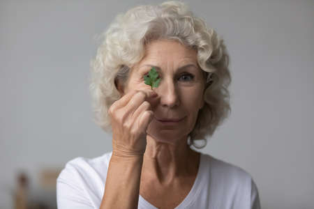 Head shot of mature woman hold parsley herb looks at camera. Skincare home natural treatment, caring for sensitive seniors skin, reduce wrinkles, increase skin regeneration, eco products cosmetics ad