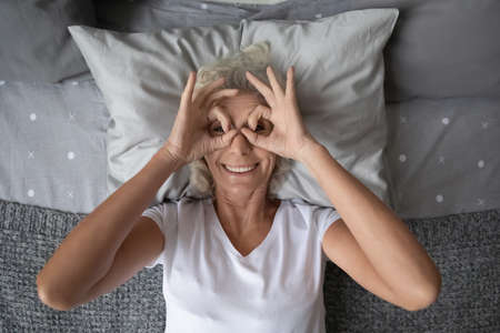 Top view grey haired elderly woman lying on pillow in bed smile look at camera through binoculars makes with fingers. Enough healthy sleep, vision correction health check up for older people concept Standard-Bild