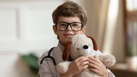 Head shot happy little cute kid boy in glasses and medical coat cuddling teddy bear toy, pretending to be veterinary doctor. Smiling small smart child looking at camera, playing with fluffy toy.