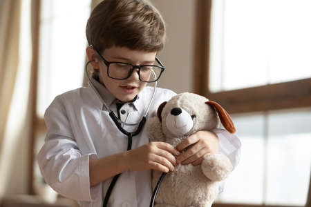 Adorable little kid boy wearing glasses and white uniform, playing doctor patient game with toy, checking lungs and heartbeat, veterinary doctor checkup childish playtime, future profession concept.
