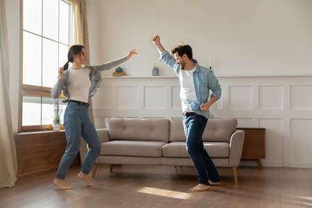 Overjoyed young married family couple homeowners dancing to music barefoot on wooden floor, celebrating moving into new apartment or freedom, enjoying active domestic hobby pastime together indoors.