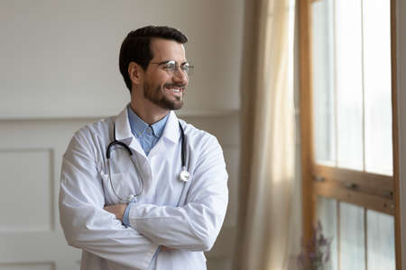Smiling young doctor in white medical uniform standing with folded hands near window, lost in thoughts. Positive handsome male head of department thinking of challenges, planning future career. 版權商用圖片