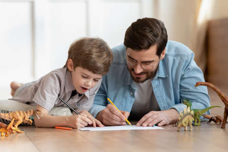 Happy little child boy lying on floor with loving dad, involved in drawing pictures in paper album using colorful pencils. Joyful father involved in hobby weekend pastime with cute small kid son.