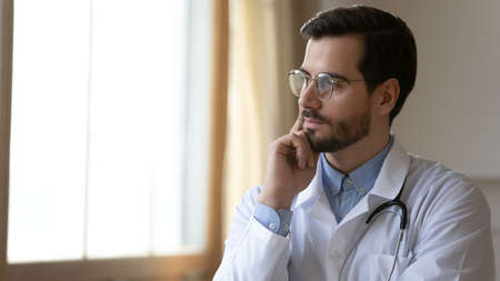 Head shot thoughtful serious young male doctor general practitioner in eyeglasses looking at window, thinking of professional challenges, healthcare medical services advertisement with copy space.