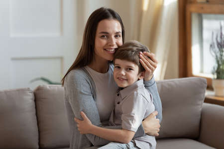 Loving affectionate young mother holding on lap little adorable son, relaxing together on comfortable couch in living room. Caring bonding nanny babysitter cuddling small child boy, looking at camera.
