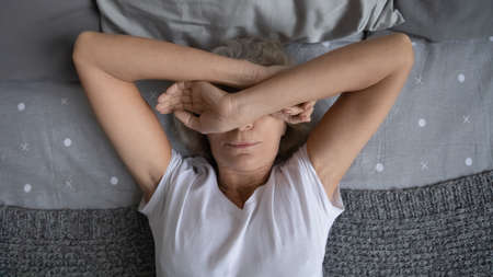 Top view aged woman lying on bed woke up at night due noisy neighbors. Mature female cover face with hands suffers from insomnia sleep disorder, has restless obsessive thoughts keep her awake concept 版權商用圖片
